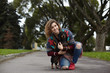 People, pets, leisure and activity. Cheerful young female in ripped jeans and warm plaid sitting on pavement on one knee, embracing her faithful four legged friend. Owner and pet dog resting outdoors
